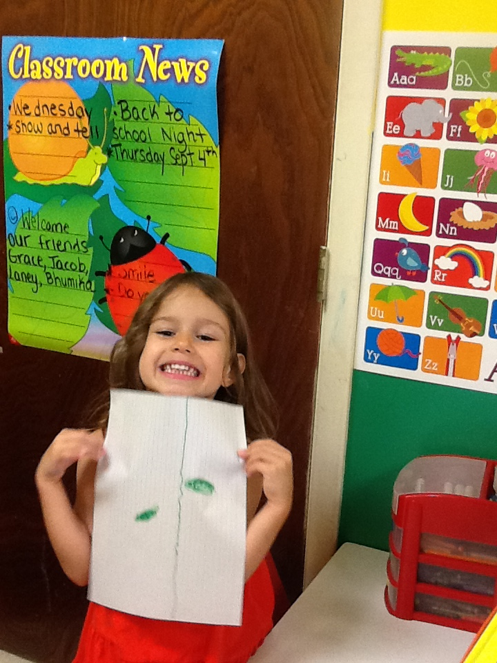 Child in our daycare program showing off her growing leaf drawing
