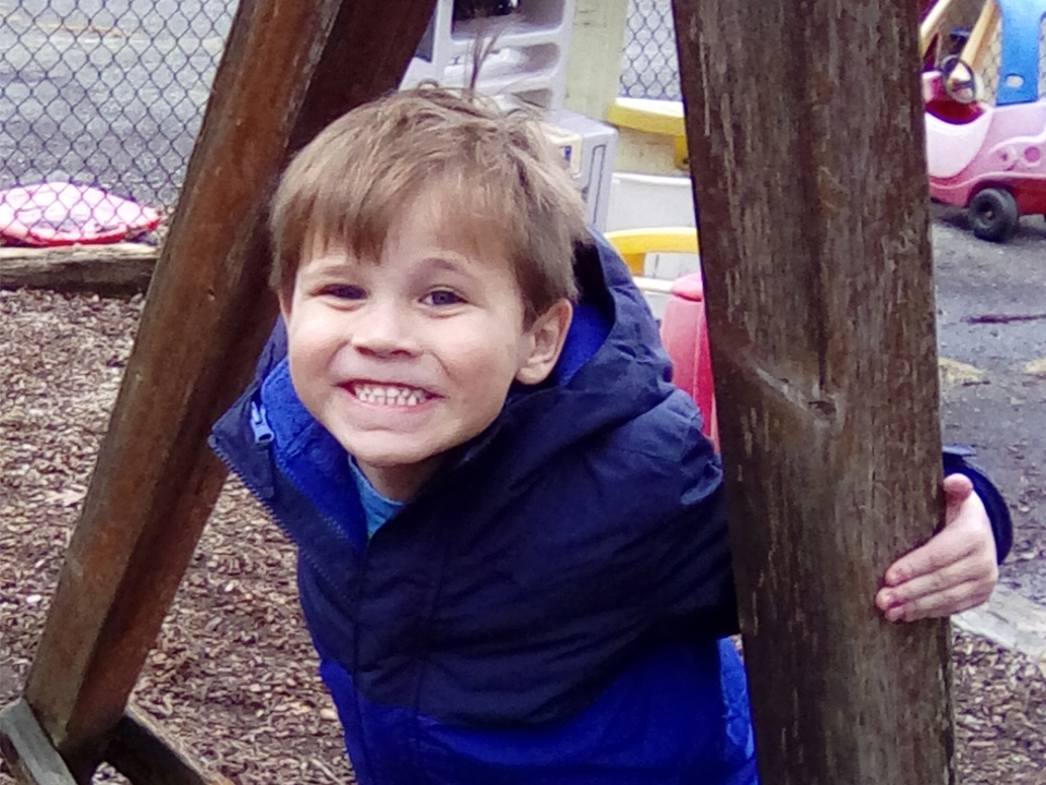 prekindergarten boy smiling big in his blue coat on the playground