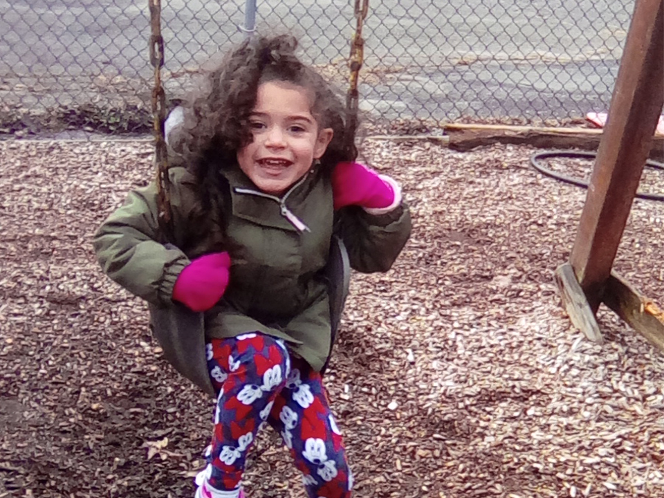 preschool girl in green jacket swinging on the playground