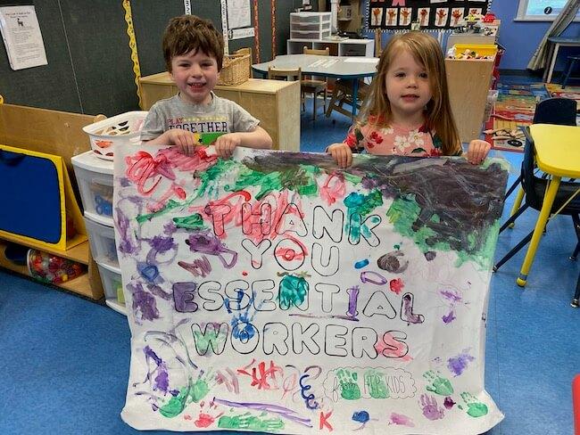 Preschool boy and Preschool Girl holding essential worker sign in the Pre-Kindergarten Classroom