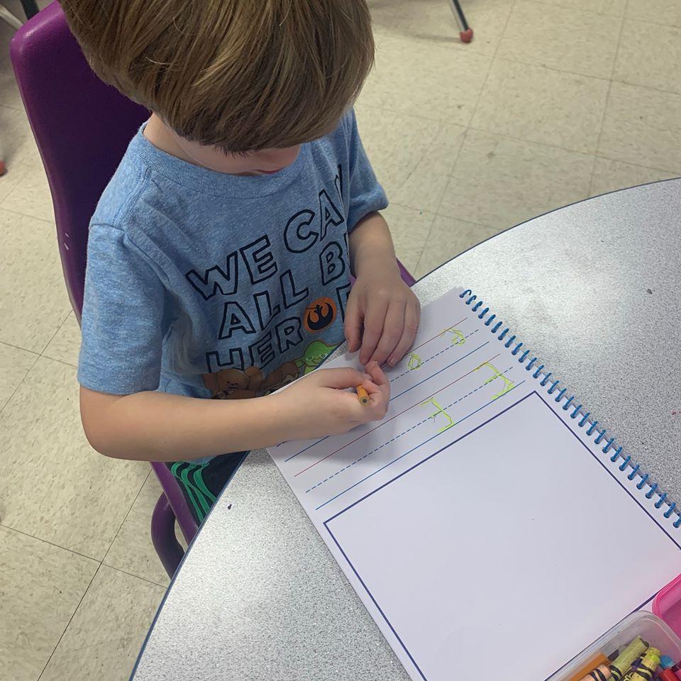 Preschool / Pre-Kindergarten Boy in Blue shirt practicing writing the letter E